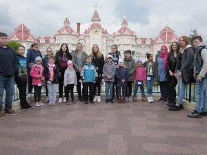 Kimnder und Eltern vor einem Disney Schloss