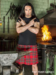 Bülent Ceylan in Schottenrock in Metalpose mit Pommesgabel-Händen
