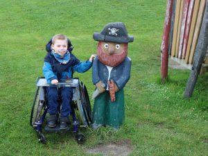 Rolli-Kind mit Räuber-Holzfigur