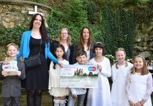 Kinder und Mütter bei der Erstkommunion mit Spendenscheck