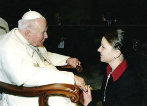 Milena kniet vor dem Papst und hält seine Hand