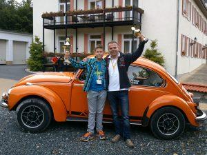 Niclas mit seinem Vater vor dem Käfer, bei de mit Pokal in nder Hand